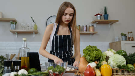 girl cooking salad with raw vegetables while looking on screen of digital tablet for online recipe, chopping mushrooms with knife. Healthy nutrition vegetarian eco food concept