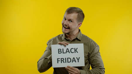 Attractive joyful man showing Black Friday inscription, advertising discounts, show thumb up, smiling looking satisfied with low prices, shopping on big sale day. Yellow background