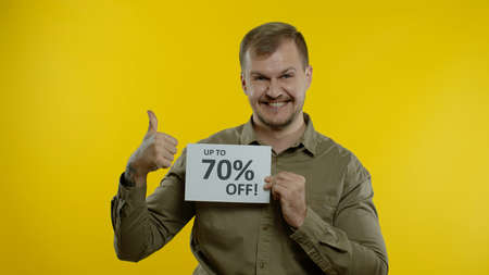Happy smiling blonde man showing Up To 70 percent Off inscriptions signs, rejoicing good discounts, low prices for online shopping sales. Studio shot on yellow background