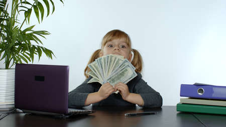 Child girl boss earns money. Little pretty boss kid hold much dollars cash in her hands on the table in the office. Finance and success business concept. White background