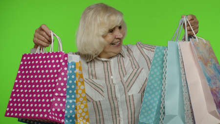 Joyful grandmother holding shopping bags, rejoicing discounts in store, enjoying shopping with low prices on Black Friday. Senior woman dancing, celebrating on chroma key background. Green screen Stock Photo