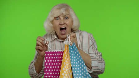 Cheerful grandmother holding shopping bags, rejoicing discounts in store, enjoying shopping with low prices on Black Friday. Senior woman dancing, celebrating on chroma key background