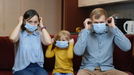 Coronavirus quarantine lockdown concept. Mother, father, daughter puts medical masks on faces at home. Family wearing protective masks. Life in covid-19 pandemic. Man, woman and child girl. Stay home Stock fotó