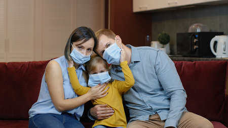 Coronavirus quarantine lockdown concept. Mother, father, daughter in medical masks on faces at home. Family wearing protective masks. Life in covid-19 pandemic. Man, woman and child girl. Stay home