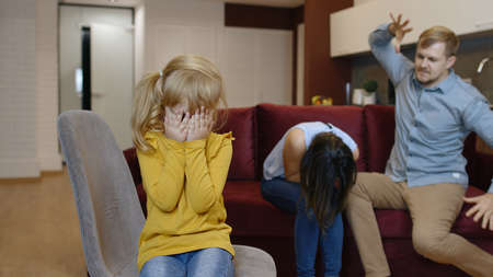 Caucasian child girl kid is suffering and crying from quarrels between parents in family at home. Angry man and woman quarrelling and fighting in living room. Problems, conflict, crisis. Parenting