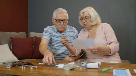 Worried old mature retired grandparents couple looking at medicine prescription, pills, tablets in blisters on table at home. Senior grandfathe, grandmother family on coronavirus quarantine lockdown