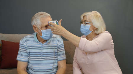 Senior couple grandfather and grandmother isolated at home during covid-19 coronavirus quarantine lockdown. Measures temperature with contactless digital thermometer. Elderly man, woman Stock fotó