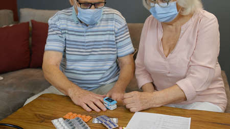 Senior couple grandparents measuring, monitoring oxygen saturation with digital pulse oximeter at home. Elderly woman and man in medical masks. Coronavirus, Covid-19 quarantine lockdown Stock fotó