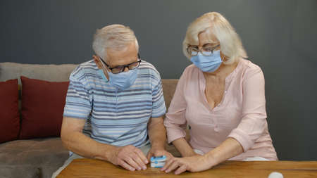 Senior couple grandfather and grandmother measuring, monitoring oxygen saturation with digital pulse oximeter at home. Elderly woman and man in medical masks. Coronavirus, Covid-19 quarantine lockdown Stock fotó