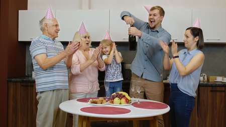 Joyful multigenerational family members with child girl kid celebrating birthday party dancing into music having fun at home kitchen. Crazy holidays. Opening champagne bottle. Senior and adult couples Stock fotó