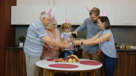 Happy multigenerational family members with child girl kid in festive cap celebrating birthday party holidays, anniversary, having fun at home kitchen. Drinking champagne. Senior and adult couples