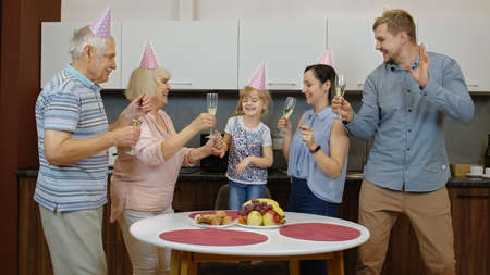 Multigenerational family members with child girl kid in festive cap celebrating birthday party holidays, anniversary, having fun, dancing at home kitchen. Drinking champagne. Senior and adult couples Stock fotó