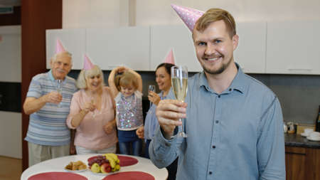 Family celebrating birthday. Portrait of positive handsome man holding glass of champagne. Happy father with wife, daughter and grandparents rejoicing holiday party at home kitchen. Slow motion Stock fotó