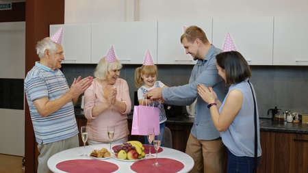 Loving mother, father and senior grandparents make surprise for cute child daughter and giving gift bag. Happy little kid girl celebrating birthday anniversary, having fun, dancing at home kitchen