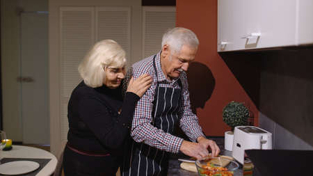 Side view of happy mature couple in love making dinner. Elderly woman hugging from back her husband cooking fresh salad standing near cutting board in kitchen at home. Senior grandmother, grandfather