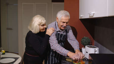 Side view of happy mature couple in love making dinner. Elderly woman hugging from back her husband cooking meal standing near cutting board in stylish kitchen at home. Senior grandmother, grandfather