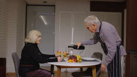 Senior retired couple having fun drinking wine and eating healty meal during romantic supper sitting in the kitchen celebrating their anniversary. Mature man and woman wife on active elderly festivity
