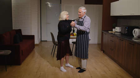Happy senior couple in love have romantic evening, dancing together in the kitchen at home, celebrating anniversary. Elderly lovely husband and wife have supper with wine, in stylish cozy interior.