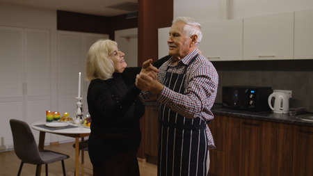 Happy senior couple in love dancing. Romantic evening supper with wine and candles, celebrating anniversary in the kitchen at home. Beautiful romantic elderly grandparents relaxing together enjoy care