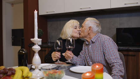 Cheerful old retired couple in love having meal at home. Aged mature grandparents eating and drinking wine during romantic dinner making a kiss sitting in modern kitchen, enjoying time together