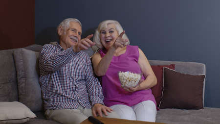 Overjoyed old mature couple football fans watching sport tv game support cheer winning soccer team sit on sofa together, happy excited senior family celebrate victory goal score view television match Stock fotó