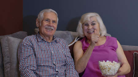 Happy senior old couple holding remote control talking laughing watching humor tv show sitting on sofa in living room, smiling elderly family enjoy funny comic television comedy movie at home together