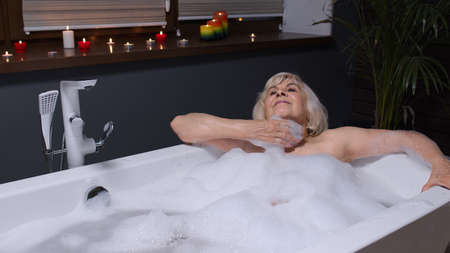 Beautiful active senior woman lying in warm bath with bubbles, enjoying relaxation. Elderly people. Cheerful happy grandmother at luxury home bathroom in a romantic setting with candles Stock fotó