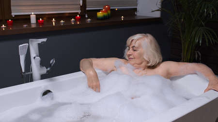 Sexy senior blonde woman grandmother is taking foamy bath in luxury bathroom with candles. Attractive elderly lady grandma strokes skin. Spa procedures self-care. Skin care. Life of active retirees