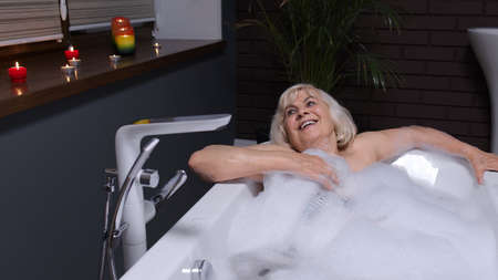 Sexy senior blonde woman grandmother is taking foamy bath in luxury bathroom with candles. Beautiful elderly lady grandma strokes skin. Spa procedures self-care. Skin care. Life of active retirees Stock fotó