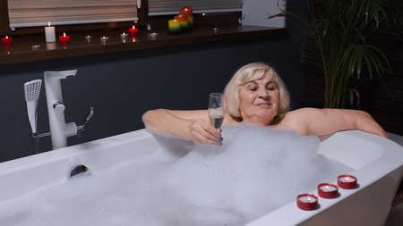 Attractive active senior woman lying in warm bath with bubbles, enjoying relaxation, drinking champagne. Cheerful happy elderly grandmother at luxury home bathroom in a romantic setting with candles