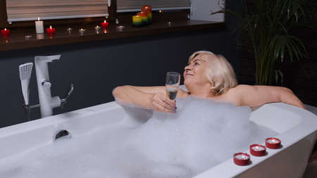 Sexy senior woman grandmother is taking foamy bath, drinking champagne in luxury bathroom with candles. Elderly lady grandma drinks white wine. Spa procedures self-care. Skin care. Life of retirees
