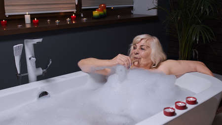 Active senior woman lying in warm bath with bubbles, enjoying relaxation, drinking champagne after a hard working day. Elderly grandmother at luxury home bathroom in a romantic setting with candles