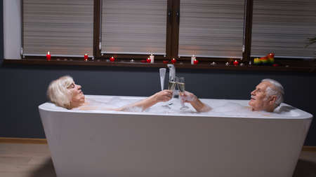 Senior couple in love lying in warm bath with bubbles, enjoying relaxation, drinking champagne. Cheerful elderly grandmother and grandfather at luxury home bathroom in romantic setting with candles