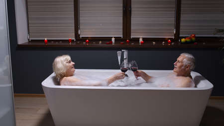 Active senior couple man and woman lying in warm bath with bubbles, enjoying relaxation, drinking red wine after a hard working day. Elderly grandmother and grandfather at luxury home bathroom