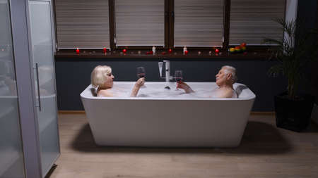 Sexy senior couple grandfather and grandmother is taking foamy bath, drinking red wine in luxury bathroom with candles. Elderly man and woman in love. Spa procedures in hotel. Honeymoon Stock fotó