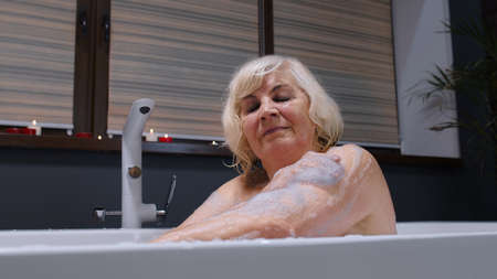 Beautiful active senior woman lying in warm bath with bubbles, enjoying relaxation. Elderly people. Side view of cheerful happy grandmother at luxury home bathroom in a romantic setting with candles