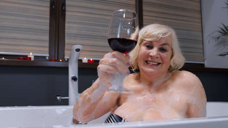 Attractive active senior woman lying in warm bath with bubbles, enjoying relaxation, drinking red wine. Cheerful happy elderly grandmother at luxury home bathroom in a romantic setting with candles Stock fotó