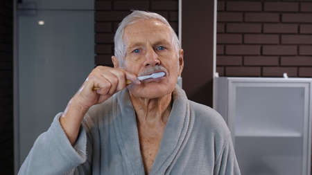 Attractive old senior man grandfather in bathrobe brushing teeth looking into mirror. Handsome elderly grandpa doing morning hygiene after shower at luxury bathroom at home. Point of view. POV shot Stock fotó