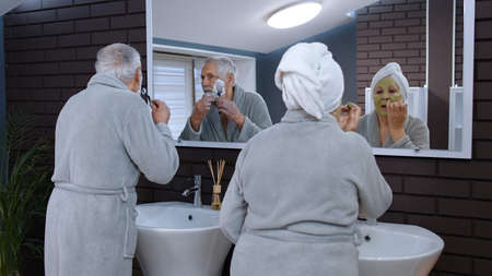 Old senior couple man and woman doing morning hygiene and looking into a mirror. Cheerful elderly grandmother applying facial green mask and grandfather shaving with manual razor blade at bathroom