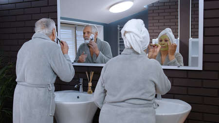 Old senior couple man and woman doing morning hygiene and looking into a mirror. Attractive elderly grandmother applying facial green mask and grandfather shaving with manual razor blade at bathroom Stock fotó