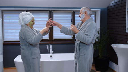 Old senior couple man and woman in bathrobe are dancing in bathroom having fun laughing enjoying leisure time and music. Elderly grandmother with facial green mask and grandfather with shaving foam Stock fotó