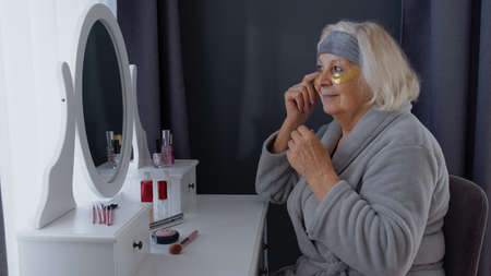 Old senior woman grandmother taking care of skin near eyes and wrinkles, putting makeup on, looking into a mirror. Elderly grandma doing make-up procedures at home. Cosmetics for retired pensioners Stock fotó