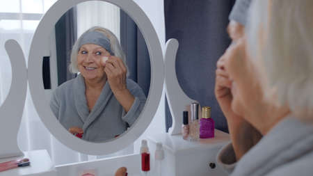 Old senior woman grandmother taking care of skin, applying anti-wrinkle foundation with sponge, putting makeup on. Elderly grandma doing make-up procedures at home. Cosmetics for retired pensioners