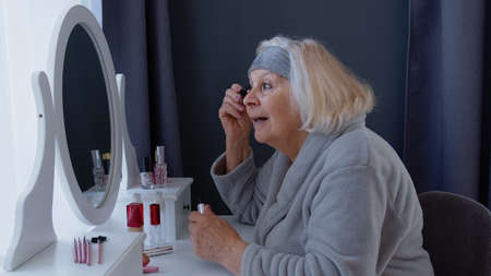 Old senior woman grandmother applying eyelash mascara, putting makeup on, taking care of skin. Elderly grandma doing make-up procedures. Cosmetics for retired pensioners