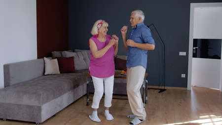 Happy senior couple dancing laughing at home. Beautiful romantic elderly grandparents relaxing having fun together celebrating anniversary enjoy care love tenderness