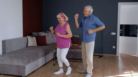 Happy old senior couple dancing celebrating retirement anniversary in modern living room at home. Grandmother and grandfather having fun dance enjoying relationship milestone celebration