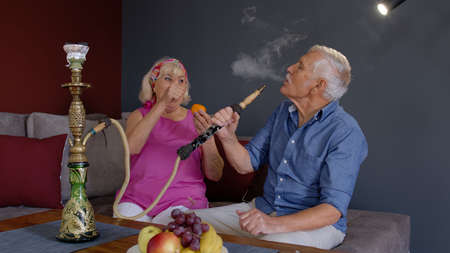 Joyful old senior couple smoking hookah, eating fruits celebrating retirement anniversary in living room at home. Elderly grandmother and grandfather having fun, enjoying relationship