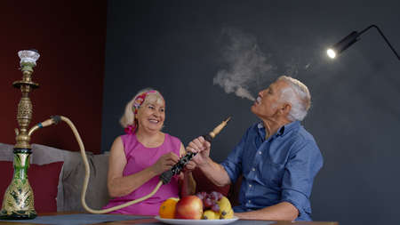 Happy stylish senior couple smoking hookah, eating fruits at home. Modern trendy elderly grandparents celebrating their anniversary relaxing having fun together enjoy care love tenderness Stock fotó