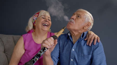 Modern trendy elderly couple smoking hookah at home. Senior grandmother and grandfather having fun relaxing enjoying relationship celebrating birthday. Life of stylish retirees pensioners