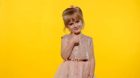 Little smiling blonde child kid girl 5-6 years old in pink dress posing thumb up with hand isolated on yellow background studio. Place for text, logo or product Archivio Fotografico